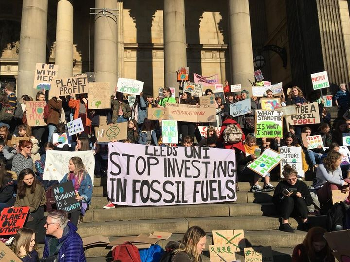 """Student climate strikers on the steps of Leeds town hall with prominent banner: """"Leeds Uni stop investing in fossil fuels"""""""